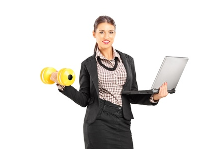 Busy smiling businesswoman holding a laptop and lifting a dumbbell isolated on white background photo