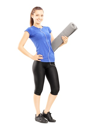 Full length portrait of a female athlete holding a mat, isolated against white background photo