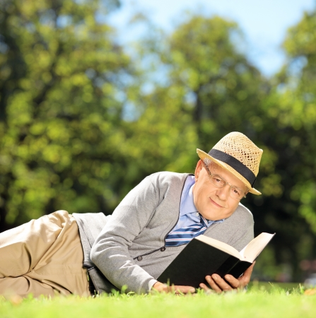 Senior gentleman lying on a grass with a book and looking at camera in park photo
