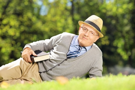 Senior gentleman with hat lying on a grass with a book and looking at camera in park photo