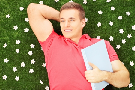 Young male with book lying on a green grass with daisy flowers photo