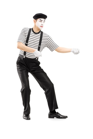 creative force: Full length portrait of a male mime artist performing pulling virtual rope isolated on white background Stock Photo