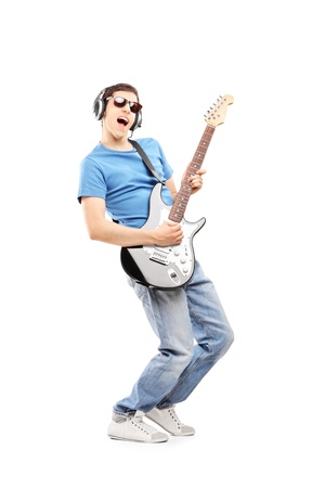 electric guitar: Full length portrait of a male musician with headphones playing an electric guitar, isolated on white background