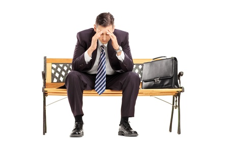 desilusion: Empresario joven decepcionante que se sienta en un banco de madera, aislado contra el fondo blanco Foto de archivo