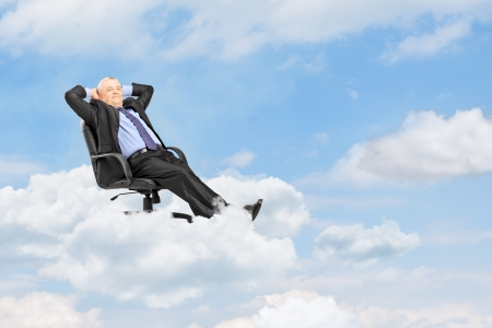 Mature businessman in suit resting in armchair and floating on a cloud photo