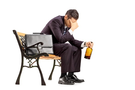 Disappointed young businessperson sitting on a wooden bench and holding a bottle isolated on white background photo