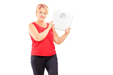 Blond mature female athlete holding a weight scale isolated on white background photo