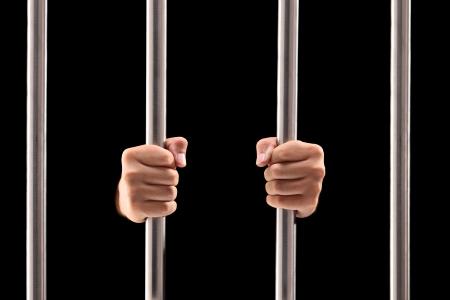 黒い背景に分離された刑務所のバーを保持している男性の手
