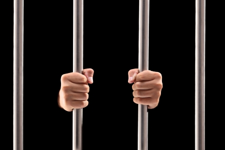 Male hands holding prison bars isolated on black background Stock Photo