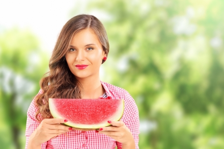 Smiling beautiful woman holding a slice of watermelon in a park photo