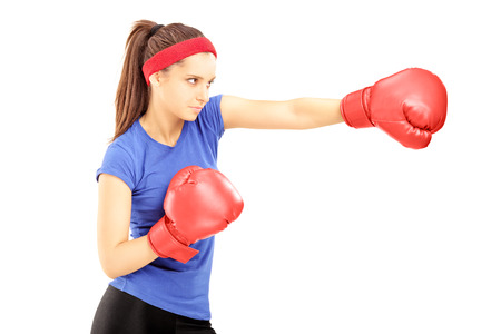 kick boxer: Female athlete hitting with red boxing gloves, isolated on white background Stock Photo