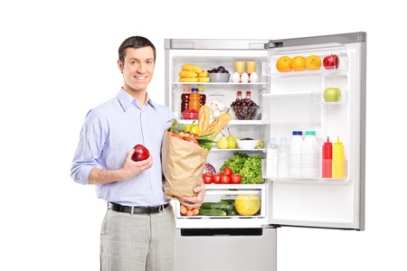 Smiling man holding a paper bag in front of refrigerator full of products and looking at camera, isolated on white background photo