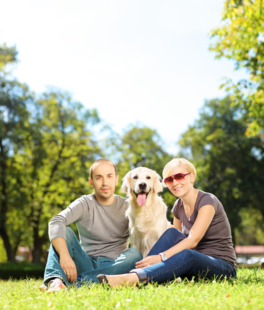 retreiver: Smiling young couple hugging a labrador retreiver dog in a park, shot with a tilt and shift lens