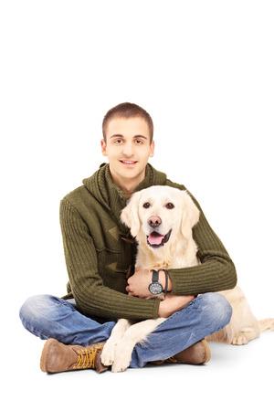 Lachende jonge man die met een retriever hond geïsoleerd tegen een witte achtergrond Stockfoto