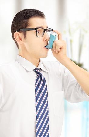 asma: Hombre joven que toma el tratamiento del asma, en el hogar