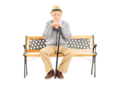 dissappointed: Sad senior man with a cane sitting on a wooden bench isolated on white background