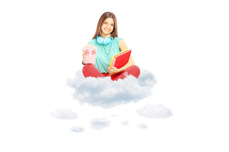 Smiling student sitting on a cloud with notebooks and popcorn box, isolated on white background photo
