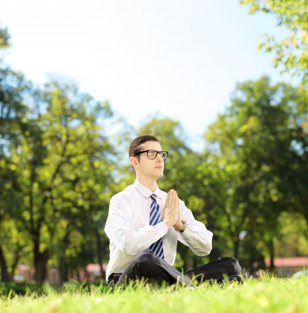 Young businessman doing yoga exercise seated on a green grass in a park, shot with a tilt and shift lens photo