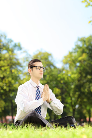 Young businessperson doing yoga exercise seated on a green grass in a park photo