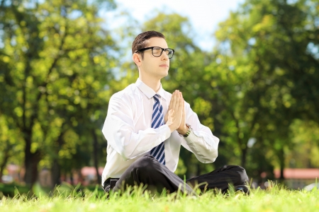 Young businessperson with eyeglasses doing yoga exercise seated on a green grass in a park  photo