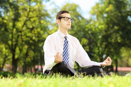 Young businessperson with eyeglasses meditating seated on a green grass in a park photo