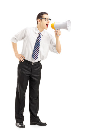 Full length portrait of an angry businessman shouting via megaphone isolated on white background photo
