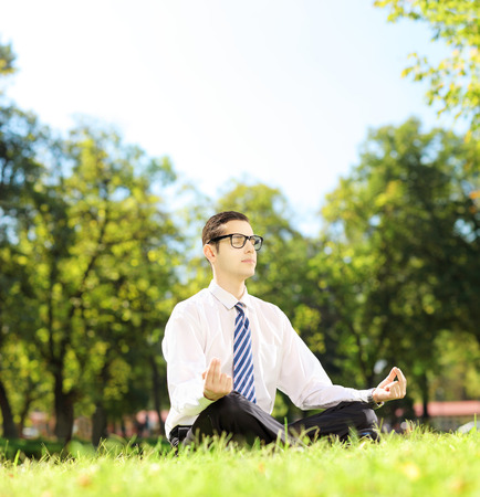 Young businessperson with eyeglasses meditating seated on a grass in a park photo