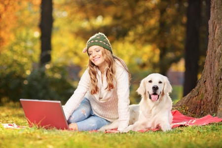 companion: Young female in a park with her labrador retriever dog working on a laptop