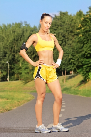 Young female runner posing on a running track in park on a sunny day photo