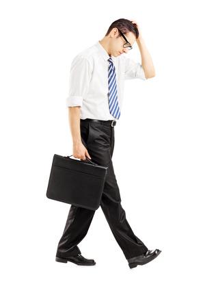 Full length Portret van een teleurgestelde zakenman wandelen met een aktetas geïsoleerd op witte achtergrond