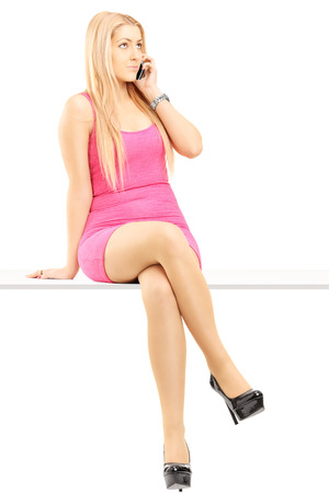 Full length portrait of an attractive blond woman talking on a mobile phone and sitting on a table isolated on white background photo