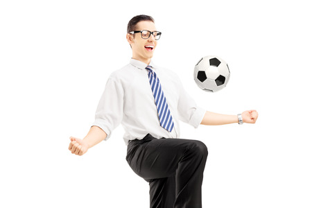 Young happy businessman playing with a soccer ball isolated on white background photo