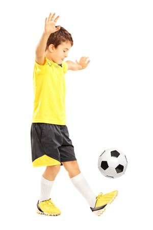 Full length portrait of a boy in sportswear joggling a soccer ball isolated on white background photo