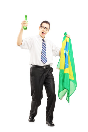 supporter: Full length portrait of an excited male with beer bottle and brazilian flag isolated on white background