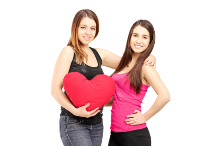 frienship: Two female best friends standing close together and holding a red heart isolated on white background