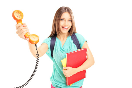 retro telephone: Young smiling female giving a telephone tube to someone isolated on white background  Stock Photo