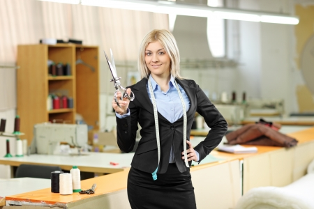Female owner of a small business standing inside a textile factory holding a scissors in her hand photo