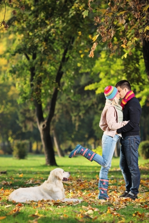 retreiver: Male and female kissing in a park and a labrador retreiver dog watching them