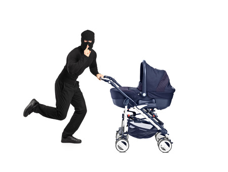 A man in robbery mask running and pushing a baby stroller with finger on the lips gesturing silence isolated on white background photo