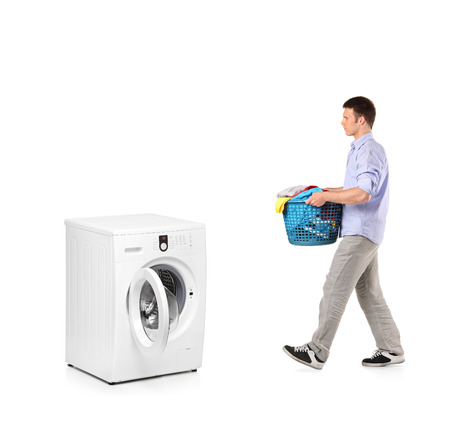 A man with a laundry basket going towards a washing machine isolated on white background photo