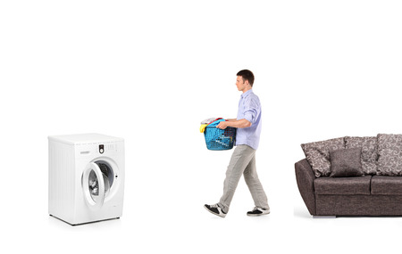 A man with a laundry basket going towards a washing machine isolated on white Stock Photo