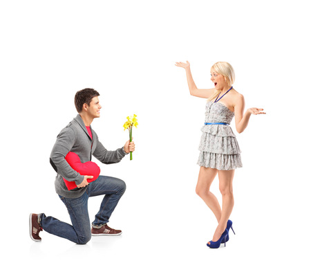 kneeling man: A young man holding bunch of flowers and his excited girlfriend isolated on white background