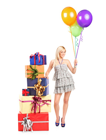 An attractive woman with ballons in her hand posing next to a pile of gifts isolated on white background photo