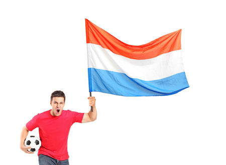 An euphoric fan holding a ball and waving a dutch flag isolated on white background photo