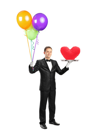Full length portrait of a butler holding a tray with a red heart shape on it and balloons isolated on white background photo