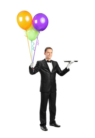 uniform attire: Full length portrait of a butler holding an empty tray and balloons isolated on white background Stock Photo