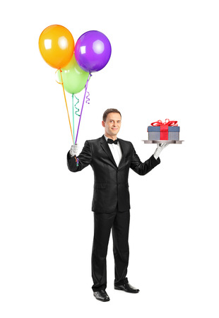 Full length portrait of a butler with bow tie carrying a tray with a gift on it and balloons isolated on white background photo