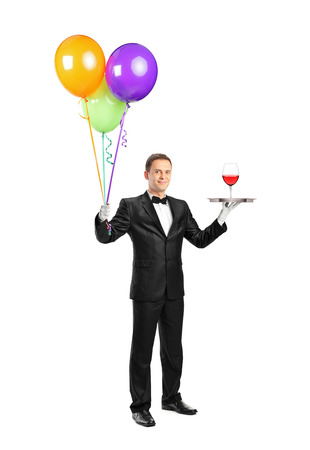 Full length portrait of a butler with bow tie carrying a tray with a wine glass on it and balloons isolated on white background photo