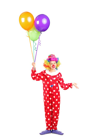 Full length portrait of a female clown, happy joyful expression on face, with a bunch of balloons isolated on white background photo