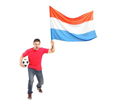 euphoric: Ritratto di lunghezza completa di un ventilatore euforico maschile in possesso di un pallone da calcio e di bandiera olandese isolato su sfondo bianco
